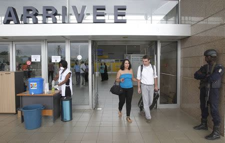 People walk past health workers wearing protective masks and gloves at the Felix Houphouet Boigny international airport in Abidjan