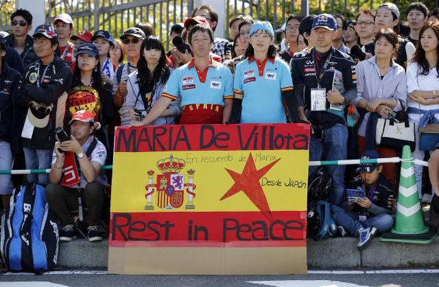 Japanese fans display a banner in the colours of the Spanish flag commemorating the late Marussia test driver Maria De Villota of Spain, at the entrance to the Suzuka circuit ahead of the Japanese F1 Grand Prix in Suzuka, western Japan October 13, 2013. Formula One drivers will hold a minute's silence at the Japanese Grand Prix on Sunday and dedicate the winner's podium to De Villota, they said on Saturday. De Villota, 33, who lost her right eye and fractured her skull in a freak accident during a straight line aerodynamic test in England in July 2012, was found dead in a hotel in her native Spain on Friday. REUTERS/Issei Kato (JAPAN - Tags: SPORT MOTORSPORT F1 OBITUARY)