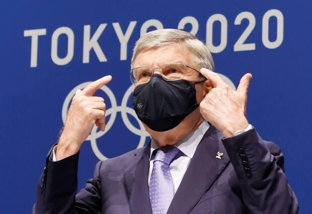 IOC president Thomas Bach gestures during a press conference ahead of the Tokyo Olympics. The Games forge on despite the risk of COVID-19 eliminating top athletes from competition.  (Shinji Kita/Kyodo News via AP - image credit)