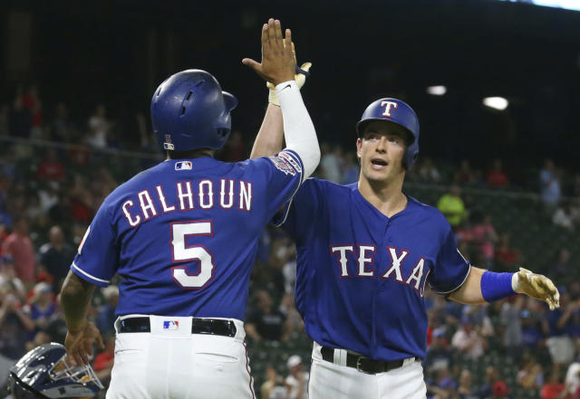 Texas Rangers' Willie Calhoun (5) greets Nick Solak at the plate after the latter's two-run home run against the Tampa Bay Rays during the fourth inning of a baseball game Tuesday, Sept. 10, 2019, in Arlington, Texas. (AP Photo/Richard W. Rodriguez)