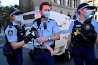 A police officer wipes away paint thrown by a protester in Sydney