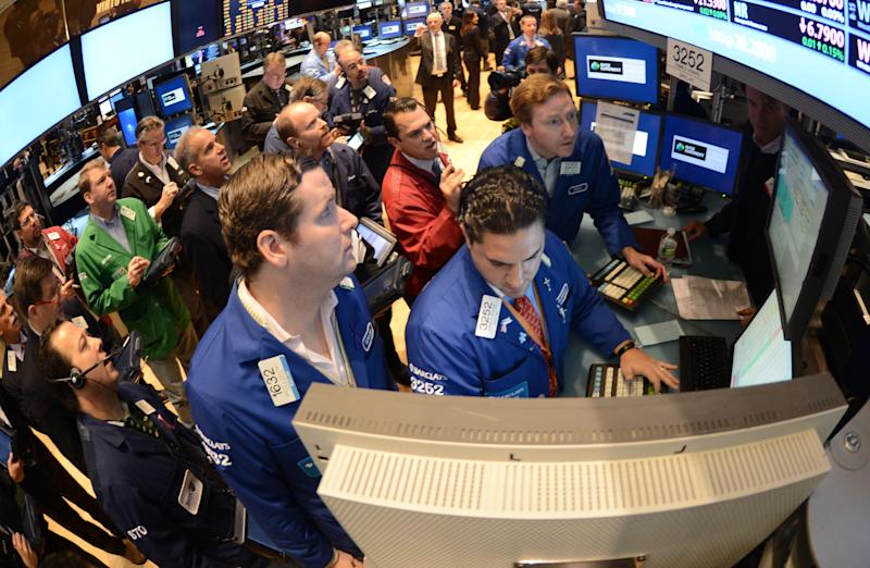 FILE - In this Thursday, Nov. 8, 2012, file photo, Gregg Maloney, left, and Ronnie Howard, center, both of Barclays, direct trading on the floor of the New York Stock Exchange, in New York  U.S. stocks eked out the tiniest of gains on Monday Nov. 12, 2012, small comfort after worries about the fiscal cliff sent the market plunging last week.  (AP Photo/Henny Ray Abrams)
