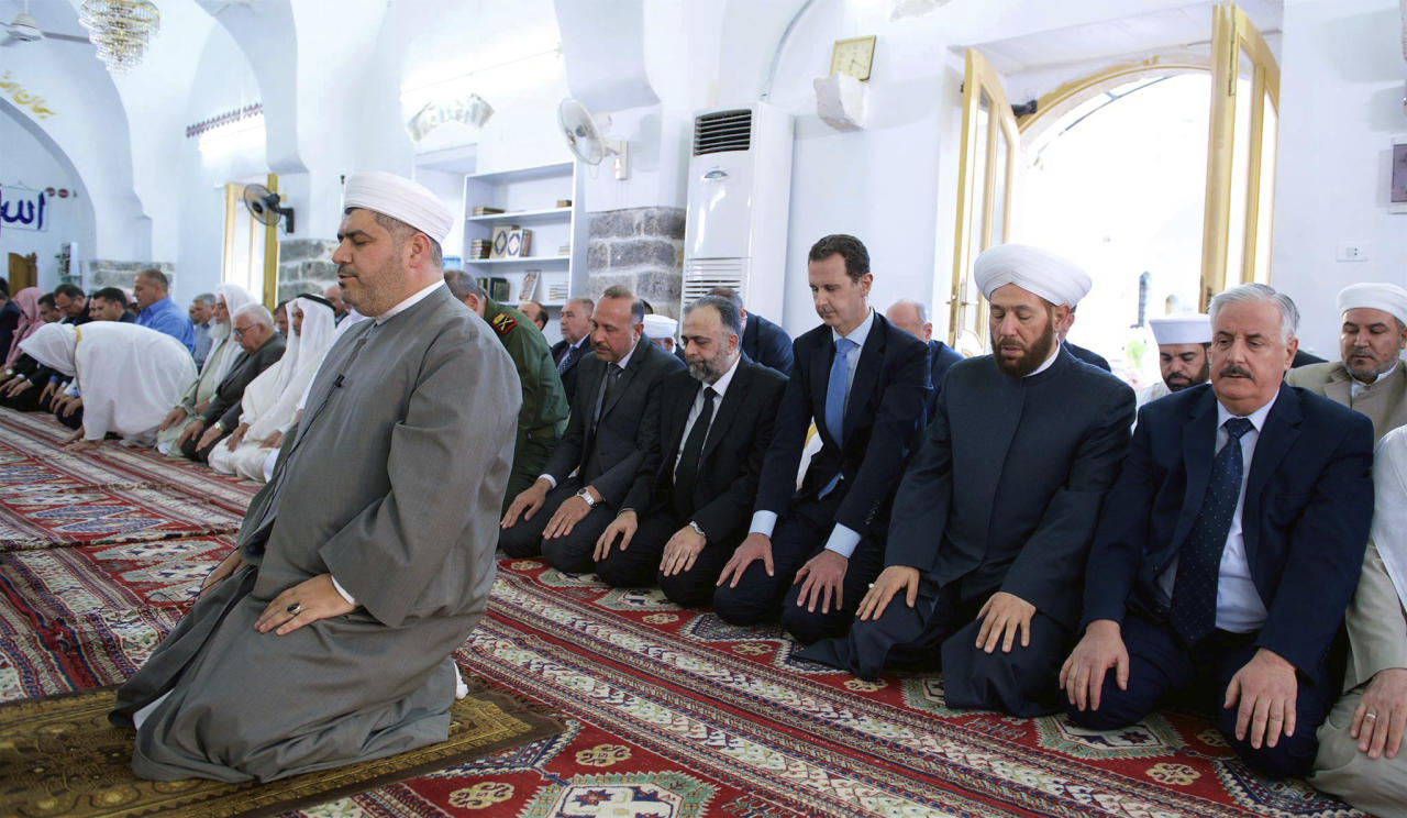 In this photo released by the Syrian official news agency SANA, Syrian President Bashar Assad, third right, prays on the first day of Eid al-Fitr, that marks the end of the Muslim holy month of Ramadan, at the Nouri Mosque in Hama, Syria, Sunday, June 25, 2017. (SANA via AP)