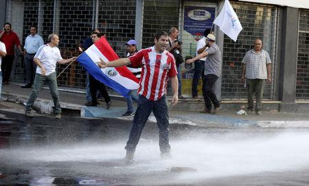 Protestors fight with the police during a demonstration against a possible change in the law to allow for presidential re-election in front of the Congress building in Asuncion, Paraguay, March 31, 2017. REUTERS/Jorge Adorno