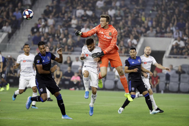 Los Angeles FC goalkeeper Tyler Miller, center right, clears the ball next to forward Diego Rossi, center left, during the first half of the team's MLS soccer match against the San Jose Earthquakes on Wednesday, Aug. 21, 2019, in Los Angeles. (AP Photo/Marcio Jose Sanchez)