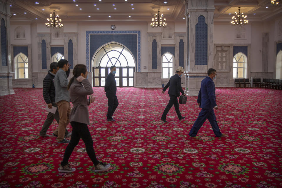 Abit Qazbay, right, an instructor at the Xinjiang Islamic Institute, and government officials walk through the prayer hall during a government organized visit for foreign journalists at the institute's campus in Urumqi in western China's Xinjiang Uyghur Autonomous Region, on April 22, 2021. Under the weight of official policies, the future of Islam appears precarious in Xinjiang, a remote region facing Central Asia in China's northwest corner. Outside observers say scores of mosques have been demolished, which Beijing denies, and locals say the number of worshippers is on the decline. (AP Photo/Mark Schiefelbein)