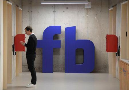 A man waits for an elevator in front of a logo at Facebook's headquarters in London, Britain, December 4, 2017. REUTERS/Toby Melville