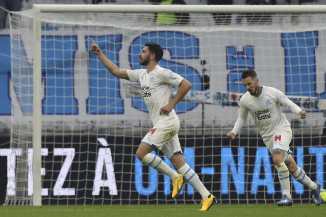 Marseille's Morgan Sanson celebrates after scoring his side's opening goal with Marseille's Dario Benedetto during the French League One soccer match between Marseille and Nantes at the Stade Velodrome in Marseille, southern France, Sunday Feb. 22, 2020. (AP Photo/Daniel Cole)