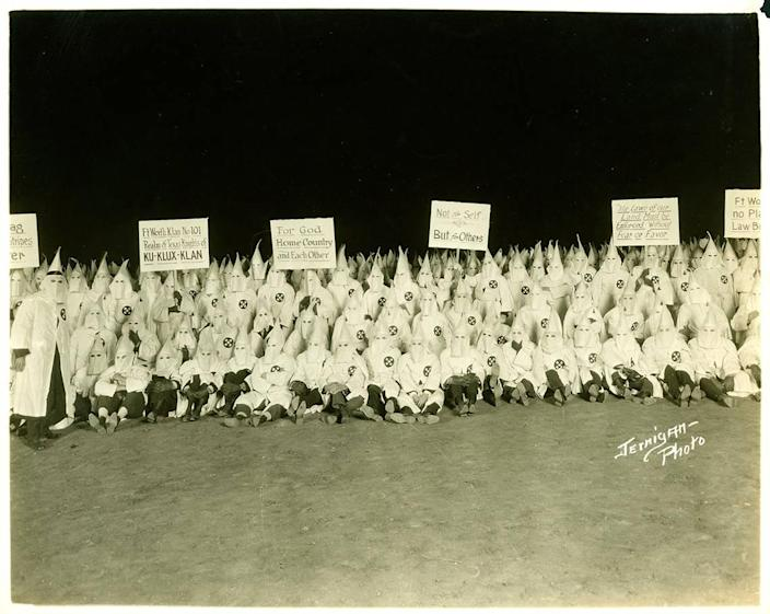 A 1920s Ku Klux Klan gathering of the Fort Worth Klan No. 101, with Klan members in robes and hoods holding signs.