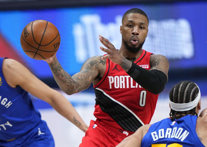 Portland Trail Blazers guard Damian Lillard (0) passes the ball against the Denver Nuggets during the second half of Game 1 of a first-round NBA basketball playoff series Saturday, May 22, 2021, in Denver. (AP Photo/Jack Dempsey)