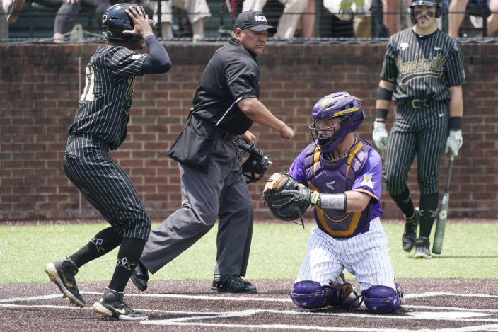Vanderbilt's Enrique Bradfield Jr. (51) reacts to being called out at the plate after trying to score on a fielder's choice against East Carolina in the eighth inning of an NCAA college baseball super regional game Friday, June 11, 2021, in Nashville, Tenn. The play was reviewed and Bradfield was ruled safe. Vanderbilt won 2-0. East Carolina catcher Seth Caddell blocks the plate. (AP Photo/Mark Humphrey)