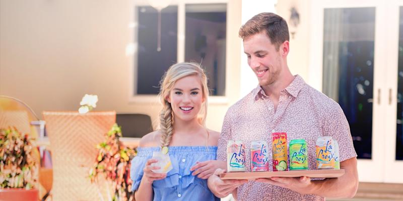 A man holding multiple cans of LaCroix, standing next to a woman holding a glass with clear liquid.