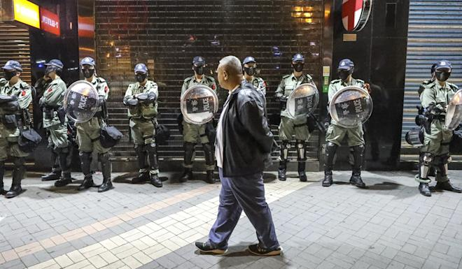 A man walks past a line of riot police in Hong Kong in October last year. Photo: Dickson Lee