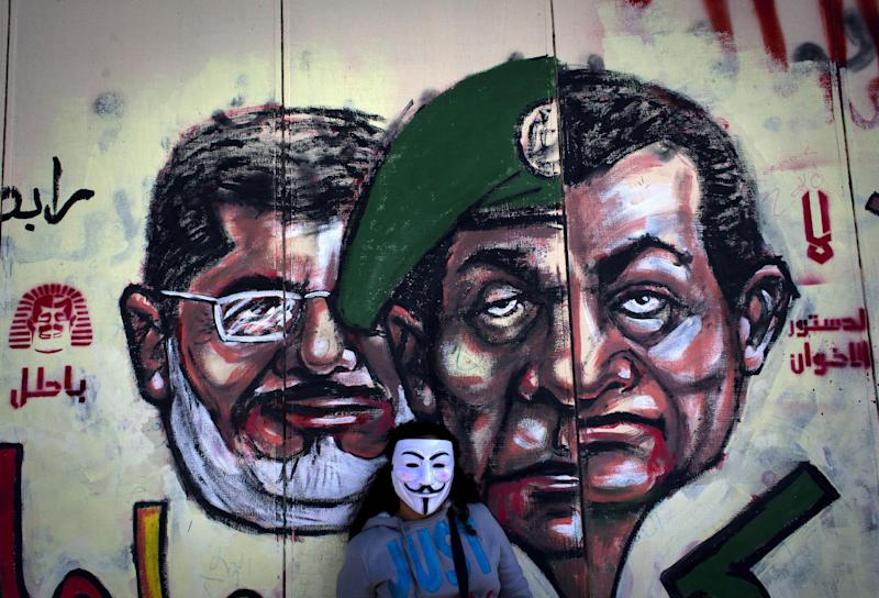 "FILE -In this Saturday, Dec. 8, 2012 file photo, an Egyptian protester wears a Guy Fawkes mask while posing for a photo next to a mural painted overnight on the exterior wall of the presidential palace depicting president Mohammed Morsi, left, former military council ruler Hussein Tantawi, center and ousted President Mubarak with Arabic that reads ""No, the brotherhood's constitution is not valid,"" in Cairo, Egypt. Egypt's newly announced criminal investigation against Mohammed Morsi is likely just the start of wider legal moves against the ousted president and his Muslim Brotherhood _ ominous prospects for a country seething with violent divisions. During three weeks of secret detention, military intelligence has extensively questioned Morsi on the inner workings of his presidency and of the Brotherhood, seeking to prove he committed crimes including handing state secrets to the Islamist group. Military officials tell The Associated Press the interrogations could land Morsi in court in lead to a renewed ban for the Brotherhood. (AP Photo/Nasser Nasser, File)"