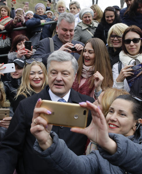 Ukrainian President Petro Poroshenko, center, poses for a selfie with a supporter after a public prayer ahead of Sunday's presidential election at the monument of Prince Volodymyr the Great Monument, the leader of Kievan Rus, in Kiev, Ukraine, Saturday, March 30, 2019. (AP Photo/Sergei Grits)