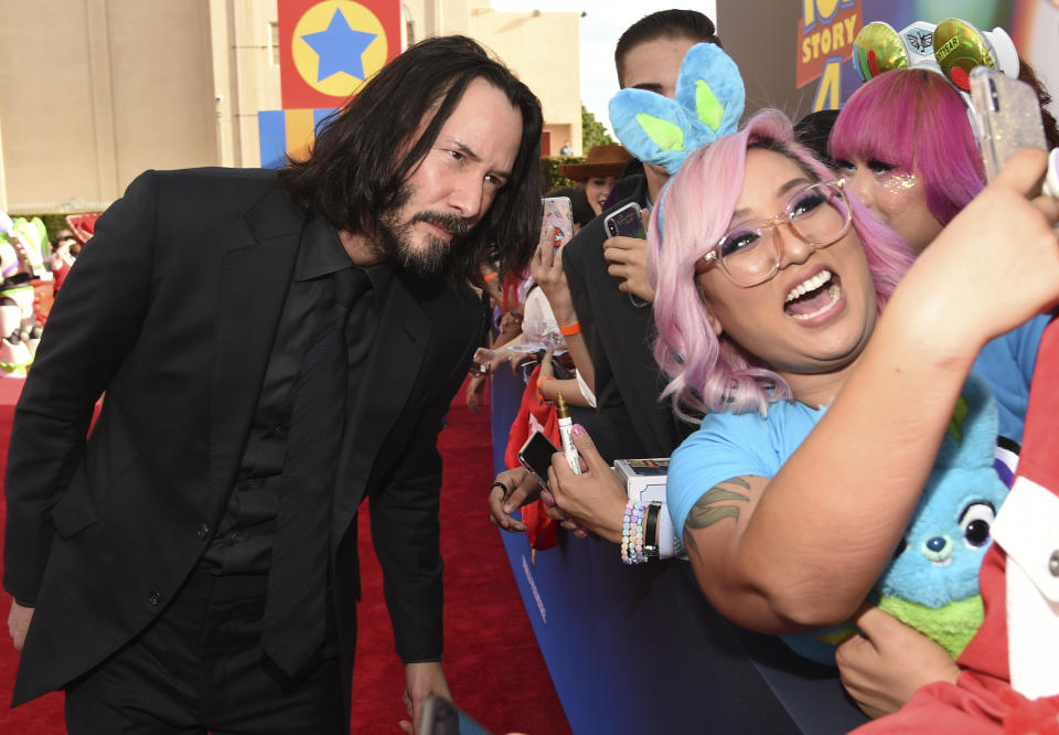 """Keanu Reeves, left, takes a selfie with a fan as he arrives at the world premiere of """"Toy Story 4"""" on Tuesday, June 11, 2019, at the El Capitan in Los Angeles. (Photo by Chris Pizzello/Invision/AP)"""
