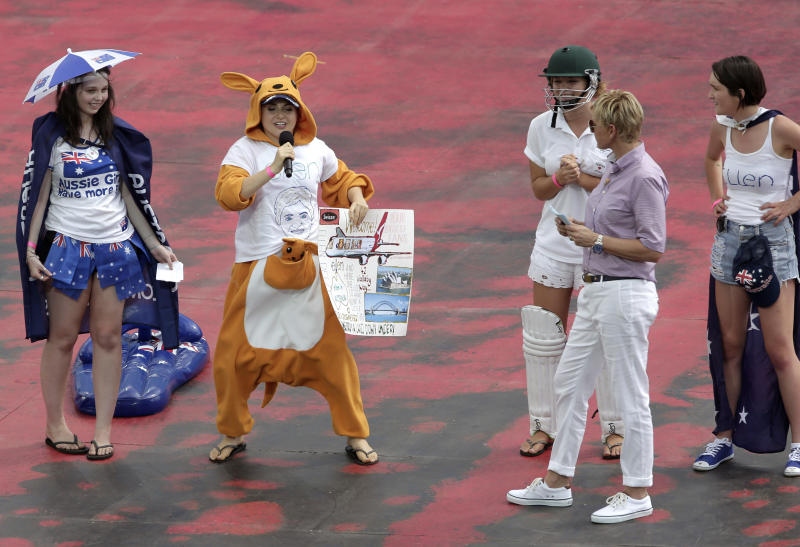 U.S. talk show host Ellen DeGeneres, second right, listens to a contestant from the crowd dressed as a kangaroo sing a song during a recording of DeGeneres' show in Sydney, Australia, Saturday, March 23, 2013.(AP Photo/Rick Rycroft)