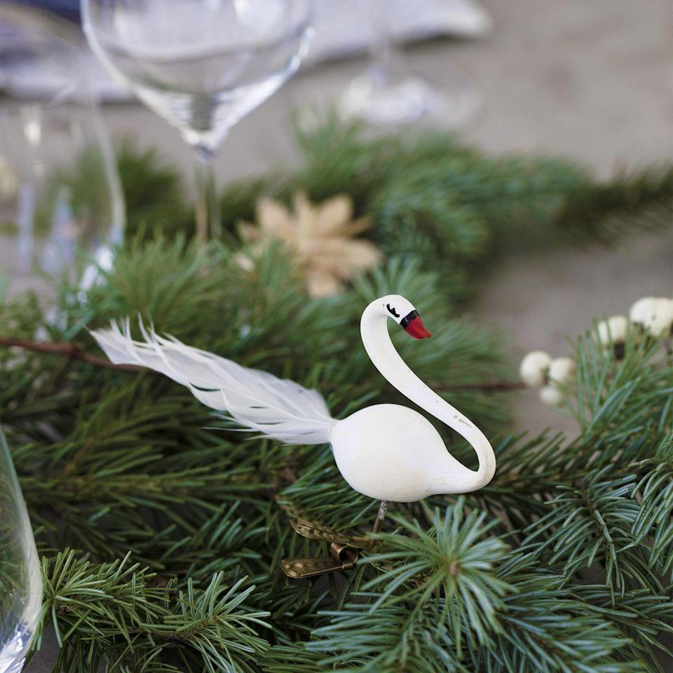 <p>Sprinkle fir twigs or place branches along the middle of the table like a garland. Nestle in bird decorations, baubles and berries for a beautifully natural centrepiece.</p>