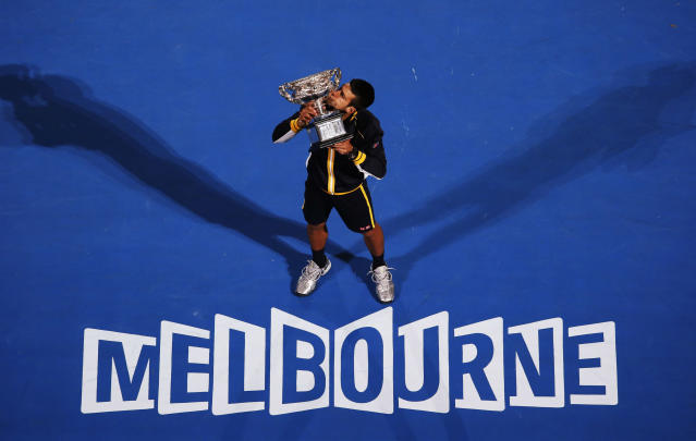 Novak Djokovic of Serbia poses with the Norman Brookes Challenge Cup after defeating Andy Murray of Britain in their men's singles final match at the Australian Open tennis tournament in Melbourne, January 27, 2013. REUTERS/David Gray (AUSTRALIA - Tags: SPORT TENNIS TPX IMAGES OF THE DAY) - RTR3D19I