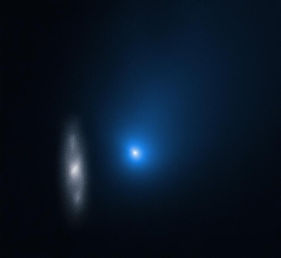 The interstellar comet Borisov appears to come face-to-face with a distant spiral galaxy in this image from the Hubble Space Telescope. Hubble captured this image on Dec. 12, as the interstellar comet was racing through the inner solar system. At the time, the object was about 260 million miles (420 million kilometers) from Earth, while the unnamed background galaxy (officially designated 2MASX J10500165-0152029), is nearly half a billion light-years away.  The galaxy appears smudged because Hubble was tracking the motion of the comet, which was zooming through space at a speed of about 109,000 mph (175,000 km/h).