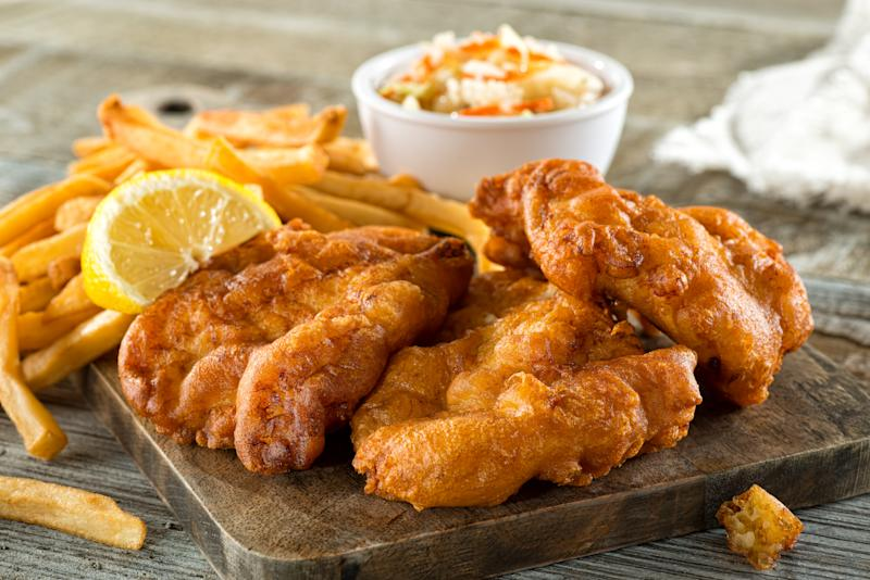 Delicious homemade fish and chips with coleslaw and lemon garnish.