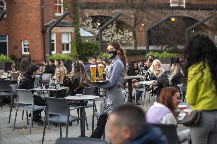 MANCHESTER, ENGLAND - APRIL 12: A waitress carries a tray of drinks in the beer garden at Dukes 92 bar on April 12, 2021 in Manchester, England. England has taken a significant step in easing its lockdown restrictions, with non-essential retail, beauty services, gyms and outdoor entertainment venues among the businesses given the green light to re-open with coronavirus precautions in place. Pubs and restaurants are also allowed open their outdoor areas, with no requirements for patrons to order food when buying alcoholic drinks. (Photo by Anthony Devlin/Getty Images)
