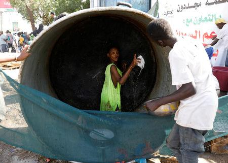 A Sudanese volunteer washes a huge cauldron used for cooking food for protesters outside the defence ministry compound in Khartoum, Sudan, April 24, 2019. REUTERS/Umit Bektas