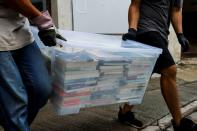 A mover collects a box of books after police search a warehouse of Student Politicism, in Hong Kong