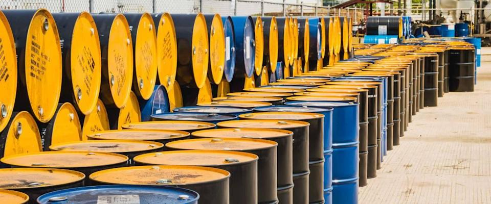 Industry oil barrels or chemical drums stacked up.container of  barrels of hydrocarbons.hazardous waste of black and blue tank oil.Stack Of Oil barrels in plant.