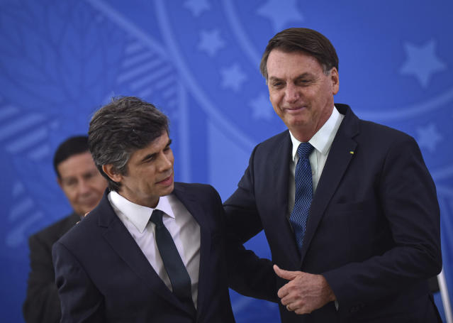 Brazil's President Jair Bolsonaro, right, embraces his newly-named Health Minister Nelson Teich at his swearing-in ceremony in Planalto palace in Brasilia, Brazil, Friday, April 17, 2020. (AP Photo/Andre Borges)