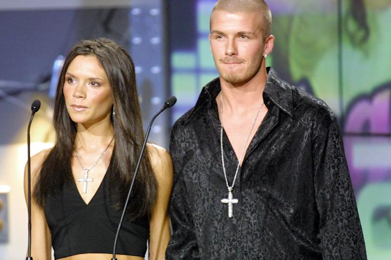 David and Victoria Beckham presenting an award in 2001 with matching diamond encrusted cross necklaces. His expression says it all.