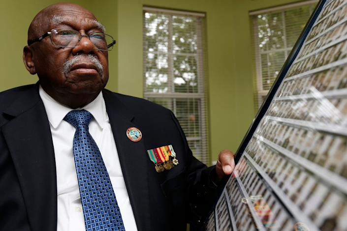 Charles Person, one of the original 13 Freedom Riders, with a poster made from the mugshots of Freedom Riders arrested in Mississippi in 1961, photographed at his home in Atlanta on April 29, 2021.