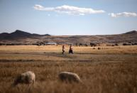 People walk through the field in the Carata peasant community, in Puno