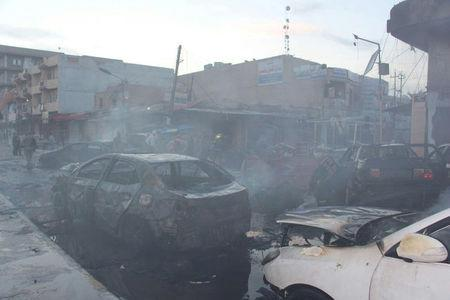 Burnt cars are seen at the site where a car bomb exploded in a crowded street in the Iraqi city of Tikrit
