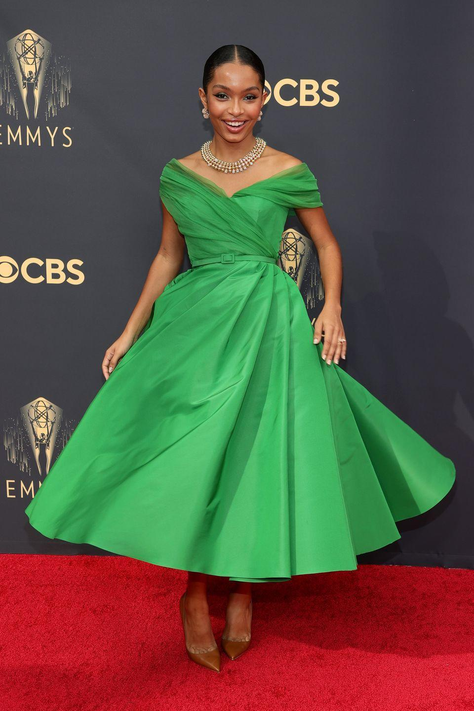 <p>Yara Shahidi looked like a glamorous Fifties film star in an ankle-length, bright green design by Dior. The actress twirled on the red carpet in the timeless design, teaming her look with a chunky necklace and brown pointed court shoes.</p>