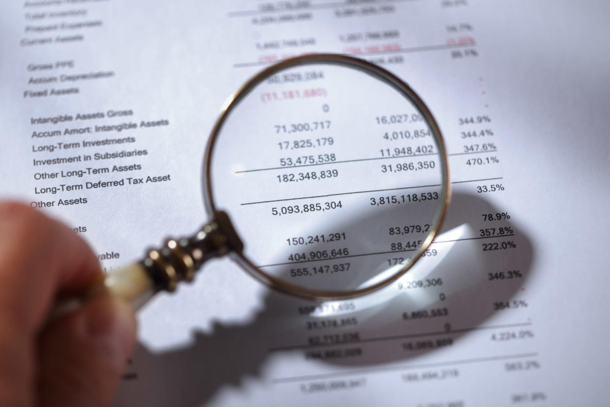 A person holding a magnifying glass over a company's balance sheet.