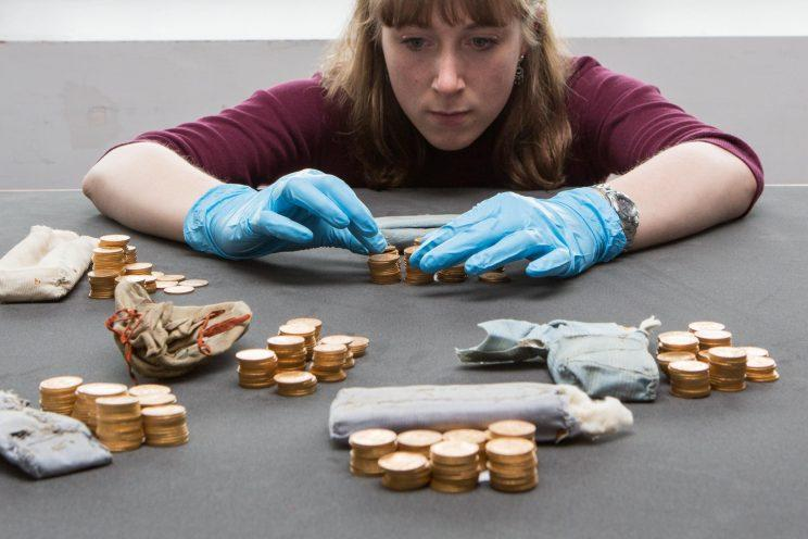 Antiques intern Emily Freeman examines the gold coins, thought to be worth £500,000 (Anita Maric/SWNS)