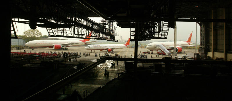 FILE- In this July 30, 2007, file photo, Air India's Boeing 777-200 LR aircraft, left and right, and Airbus A-321, center, stand parked during an event at the Chattrapati Shivaji International airport in Mumbai, India, Monday. Cash-starved Air India is putting its crew on a diet, changing their inflight menu to special low-fat meals. Dhananjay Kumar, the state-run airline's spokesman, said Wednesday, Sept. 18, 2019, that the objective is to provide healthy and cost-effective meals to crews on domestic and international flights. In 2009, the airline fired 10 air hostesses for being overweight after they failed to get back in shape three years after they were switched to ground crew jobs. (AP Photo/Gautam Singh, File)