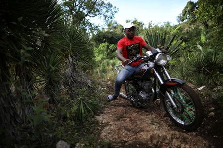 A man rides a motorbike across the trail that connects Boucan Ferdinand with the border between Haiti and Dominican Republic, on the outskirts of Boucan Ferdinand, Haiti, April 8, 2018. REUTERS/Andres Martinez Casares