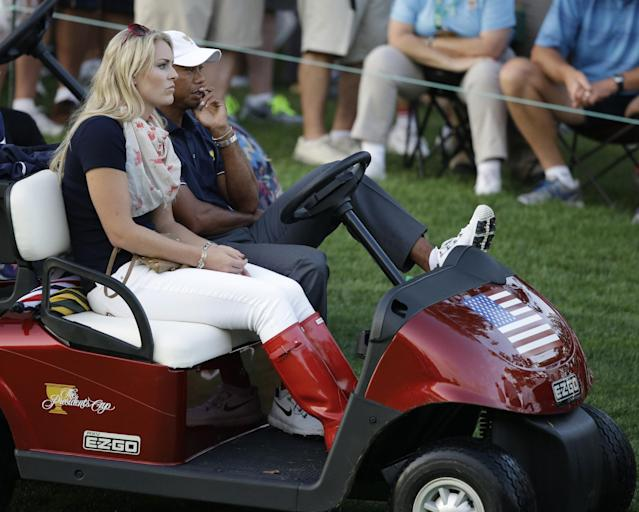 United States' Tiger Woods and his girlfriend, skier Lindsey Vonn watch the action on the 18th hole from a golf cart during a four-ball match at the Presidents Cup golf tournament at Muirfield Village Golf Club on Thursday, Oct. 3, 2013, in Dublin, Ohio. (AP Photo/Darron Cummings)
