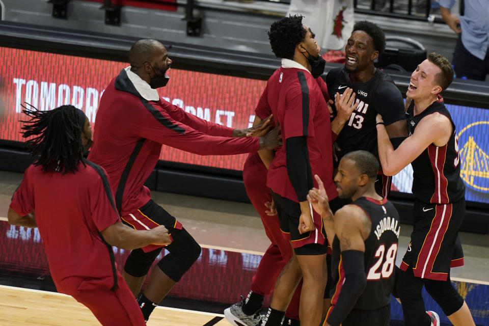 Miami Heat center Bam Adebayo (13) is mobbed by teammates after he made the winning shot against the Brooklyn Nets at the end of an NBA basketball game, Sunday, April 18, 2021, in Miami. (AP Photo/Wilfredo Lee)