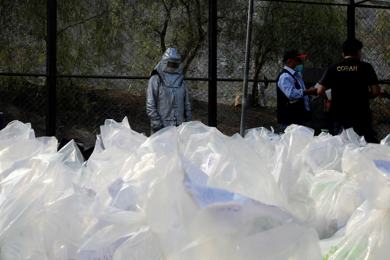 Anti-narcotics workers stand in front of bags containing cocaine and other drugs during an incineration of about 7.9 tons, seized during police operations, according to the Interior Ministry, in Lima, Peru February 2, 2017. REUTERS/Guadalupe Pardo