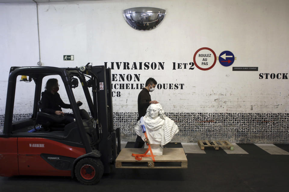 Workers transport a bust of Guillaume de Lamoignon by French sculptor Francois Girardon, in the Louvre museum, in Paris, Wednesday, Feb. 17, 2021. The forced closure has granted museum officials a golden opportunity to carry out long-overdue refurbishments that were simply not possible with nearly 10 million visitors a year. (AP Photo/Thibault Camus)