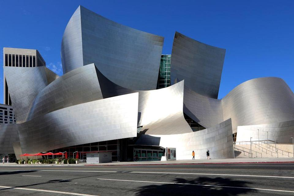 """<p>The adjectives to describe Frank Gehry's 2003 <a href=""""https://illumin.usc.edu/curves-of-steel-catia-and-the-walt-disney-concert-hall/"""" rel=""""nofollow noopener"""" target=""""_blank"""" data-ylk=""""slk:concert hall in Los Angeles"""" class=""""link rapid-noclick-resp"""">concert hall in Los Angeles</a> flow as freely as the form of the structure. Known for using a mix of materials, the Walt Disney Concert Hall features a stainless steel skin, which was chosen for its ability to curve as much as its cost savings. Inside, the hall takes on a completely different appearance with <a href=""""https://www.exp1.com/blog/walt-disney-concert-hall-architectural-gem-of-downtown-la/"""" rel=""""nofollow noopener"""" target=""""_blank"""" data-ylk=""""slk:Douglas fir and oak"""" class=""""link rapid-noclick-resp"""">Douglas fir and oak</a>, which helps with its acoustics. There's a dichotomy of Gehry embracing shape throughout the design for both acoustics and aesthetics.</p>"""