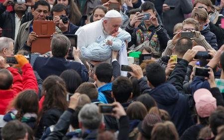Pope Francis kisses a baby as he leads the weekly general audience in Saint Peter's Square at the Vatican
