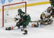 Minnesota Wild's Jared Spurgeon, left, scores a power play goal against Vegas Golden Knights' goalie Marc-Andre Fleury, right, in the first period of an NHL hockey game Tuesday, Feb. 11, 2020, in St. Paul, Minn. (AP Photo/Jim Mone)