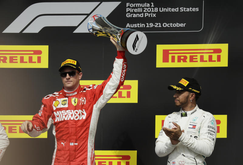 Ferrari driver Kimi Raikkonen, of Finland, holds the trophy after winning the Formula One U.S. Grand Prix auto race at the Circuit of the Americas, Sunday, Oct. 21, 2018, in Austin, Texas. Mercedes driver Lewis Hamilton, right, of Britain, finished third. (AP Photo/Eric Gay)