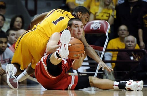 Ohio State's Aaron Craft (4) strips the ball from Minnesota's Andre Hollins (1) in the first half during an NCAA college basketball game in Minneapolis on Tuesday, Feb. 14, 2012. (AP Photo/Hannah Foslien)