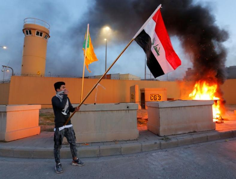 A protester holds an Iraqi flag during a protest to condemn air strikes on bases belonging to Hashd al-Shaabi (paramilitary forces), outside the main gate of the U.S. Embassy in Baghdad