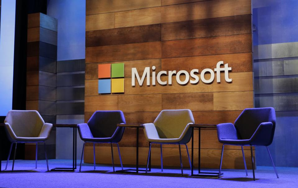 The Microsoft logo is shown above chairs for speakers, Wednesday, Dec. 2, 2015, at Microsoft's annual shareholders meeting in Bellevue, Wash. (AP Photo/Ted S. Warren)